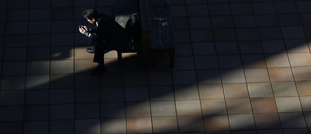 A man uses a smartphone on a street in Tokyo November 21, 2013. The Bank of Japan maintained its ultra-loose monetary policy on Thursday and reiterated the economy is recovering moderately, in a nod to signs of a pick-up in exports that is key to sustaining the momentum generated by premier Shinzo Abe's stimulus. REUTERS/Issei Kato (JAPAN - Tags: BUSINESS EMPLOYMENT TELECOMS TPX IMAGES OF THE DAY) - GM1E9BL110001