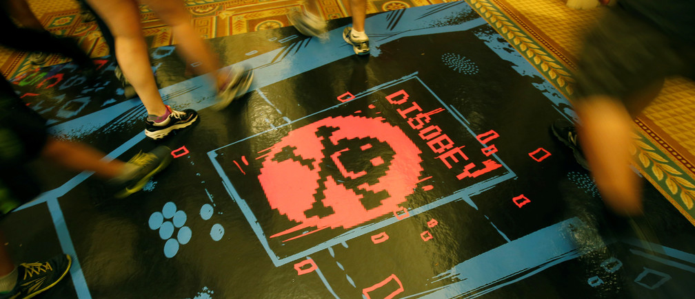 People walk past a floor graphic during the Def Con hacker convention in Las Vegas, Nevada, U.S. on July 29, 2017. REUTERS/Steve Marcus - RC1B13C62450