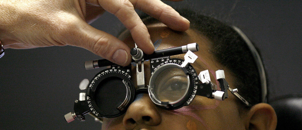 A doctor checks the eyesight of Carin Bell, one of a group of about 50 children who were being tested at the Red Cross Children Hospital in Cape Town, October 11, 2007. World Sight Day 2007 is observed on October 11 and focuses on the issues of childhood blindness.  REUTERS/Mike Hutchings (SOUTH AFRICA) - GM1DWIROVTAA
