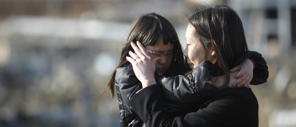 Wakana Kumagai, 7, and her mother Yoshiko cry as they visit the spot where their house, which was washed away by the March 11, 2011 tsunami, used to stand in Higashimatsushima, Miyagi prefecture March 11, 2012, to mark the first anniversary of an earthquake and tsunami that killed thousands and set off a nuclear crisis. Kumagai's father Kazuyuki called his wife Yoshiko just after the March 11, 2011 earthquake to tell her to take the children to Omagari elementary school which was serving as a shelter. He was found near the shelter four days after the tsunami, Yoshiko said.   REUTERS/Toru Hanai (JAPAN - Tags: ANNIVERSARY DISASTER) - GM1E83B19S901