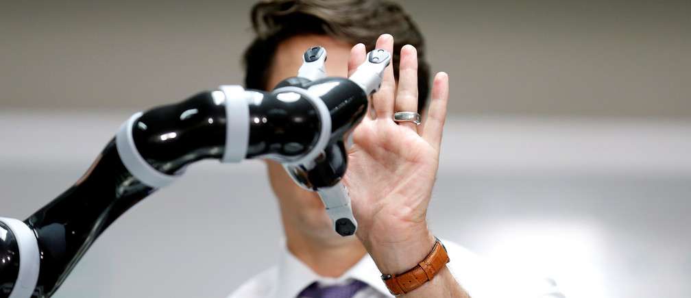 Canadian Prime Minister Justin Trudeau high fives a robotic arm as he takes part in a robotics demonstration at Kinova Robotics in Boisbriand, Quebec, Canada March 24, 2017.  REUTERS/Christinne Muschi     TPX IMAGES OF THE DAY - RC18BB86E610