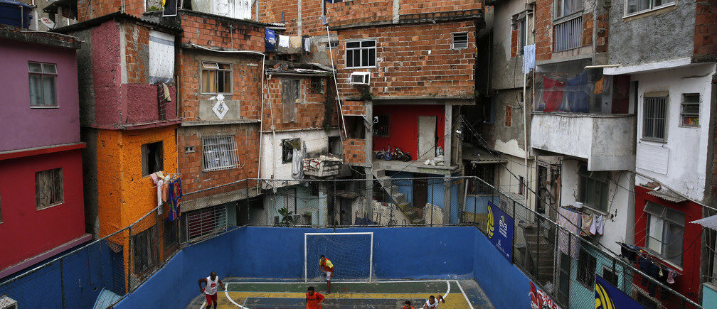 People take part in a soccer match held at the Tavares Bastos slum in Rio de Janeiro May 18, 2014. The World Cup will be held in 12 cities in Brazil from June 12 till July 13. REUTERS/Pilar Olivares (BRAZIL - Tags: SPORT SOCCER TPX IMAGES OF THE DAY)FOR BEST QUALITY IMAGE ALSO SEE: GF10000109702 - GM1EA5J074H01