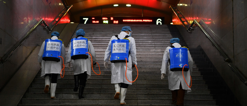 Workers with sanitizing equipment walk up a flight of stairs as they disinfect a railway station while the country is hit by an outbreak of the new coronavirus, in Kunming, Yunnan province, China February 4, 2020. Picture taken February 4, 2020. cnsphoto via REUTERS   ATTENTION EDITORS - THIS IMAGE WAS PROVIDED BY A THIRD PARTY. CHINA OUT.