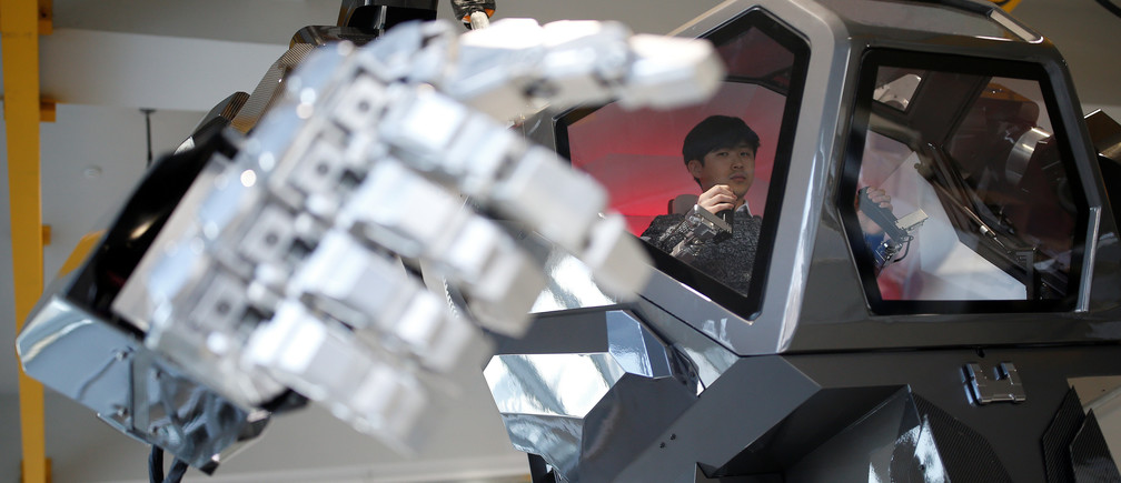 """An employee controls the arms of a manned biped walking robot """"METHOD-2"""" during a demonstration in Gunpo, South Korea, December 27, 2016."""