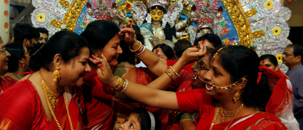 """A girl watches as Hindu women apply """"sindhur"""", or vermillion powder, on each others face after worshipping the idol of the Hindu goddess Durga on the last day of the Durga Puja festival in Kolkata, India October 11, 2016. REUTERS/Rupak De Chowdhuri"""