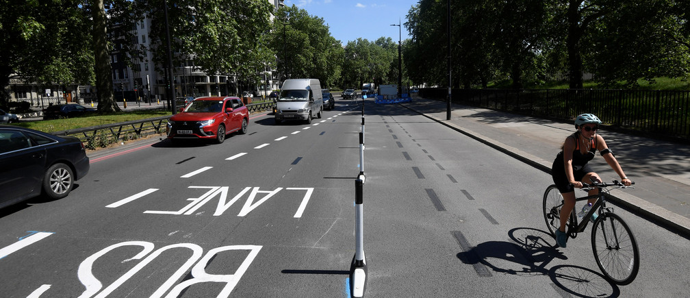 A cyclist rides along a newly created bicycle lane by Transport for London on Park Lane in London, following the outbreak of the coronavirus disease (COVID-19), London, Britain, May 21, 2020. REUTERS/Toby Melville - RC22TG9B5BLJ
