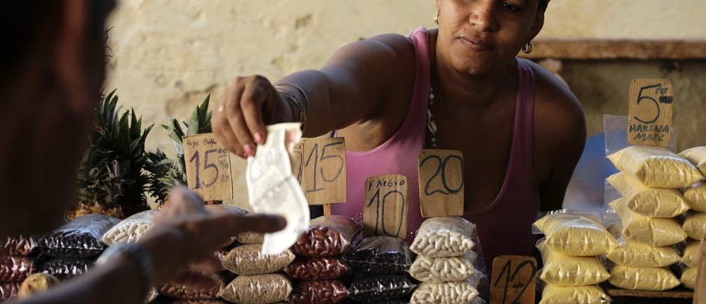 A vendor hands change back to a customer at her market stall with price tags marked in Cuban pesos in Havana October 23, 2013. Cuba took the first step towards scrapping its two-tier currency on October 22, 2013, in a move which could boost local workers' income and remove a major hurdle for importers and exporters. Cuba's convertible peso (CUC) is pegged to the U.S. dollar, while the local peso (CUP) is valued at a fraction of the greenback's value, angering the population which is paid in the latter, and complicating accounting, the evaluation of performance, and trade for state companies. REUTERS/Desmond Boylan (CUBA - Tags: SOCIETY BUSINESS AGRICULTURE) - RTX14LFW