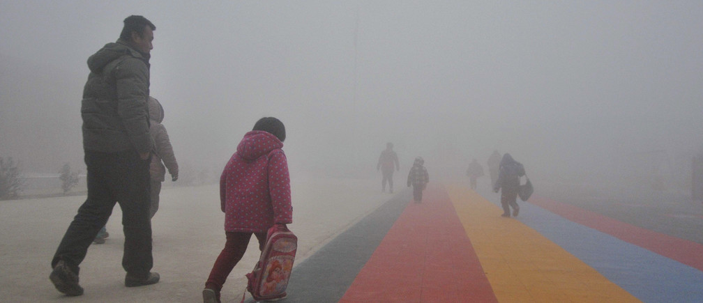 Parents walk primary school students to school amid thick haze in Chiping county, Shandong province January 16, 2015. The National Meteorological Center of China Meteorological Administration (CMA) issued a yellow smog alert early on Wednesday, predicting that smog will persist in most parts of the country for the upcoming days, Xinhua News Agency reported. REUTERS/China Daily (CHINA - Tags: ENVIRONMENT SOCIETY EDUCATION TPX IMAGES OF THE DAY) CHINA OUT. NO COMMERCIAL OR EDITORIAL SALES IN CHINA - GM1EB1G0ZOD01