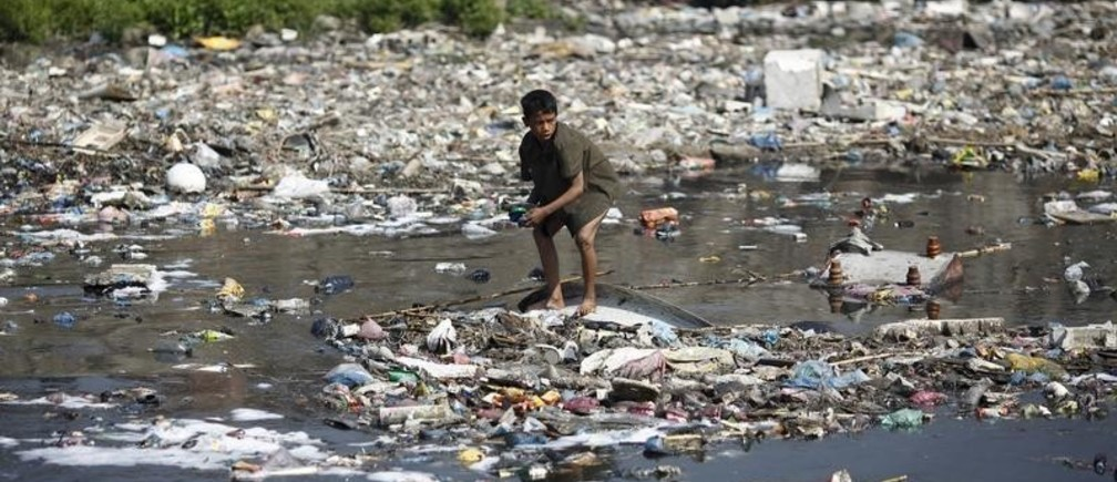 "A boy looks for plastic bottles at the polluted Bagmati River in Kathmandu March 22, 2013. This year's theme for World Water Day, which falls on March 22, is ""Water Cooperation"" and is in line with the celebration of the International Year of Water Cooperation. REUTERS/Navesh Chitrakar (NEPAL - Tags: SOCIETY ENVIRONMENT) - RTR3FBFC"