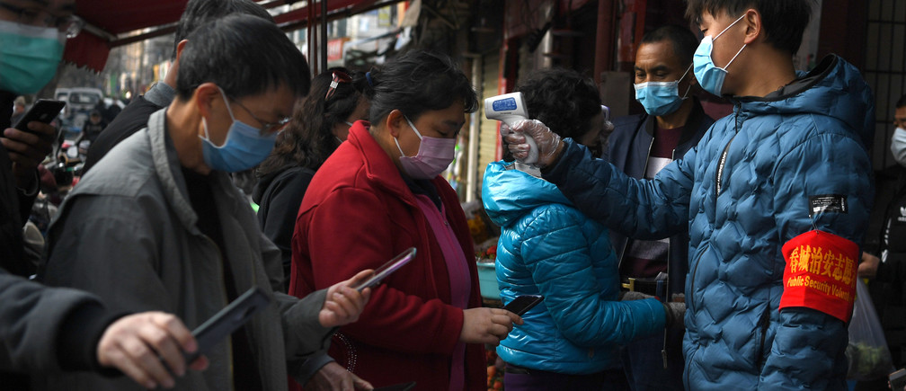 People wearing face masks scan a QR code to submit their personal information while security volunteers check their temperatures at an entrance of a grocery market, as the country is hit by an outbreak of the novel coronavirus, in Kunming, Yunnan province, China February 24, 2020. REUTERS/Stringer CHINA OUT. - RC268F9T0QX1