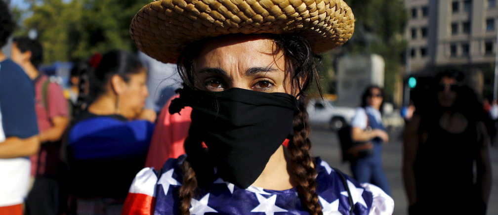 An activist depicting a farmer wears a U.S. flag during a rally against the Trans-Pacific Partnership (TPP) trade deal in front of the government house at Santiago, Chile, February 4, 2016. REUTERS/Ivan Alvarado - RTX25IWJ