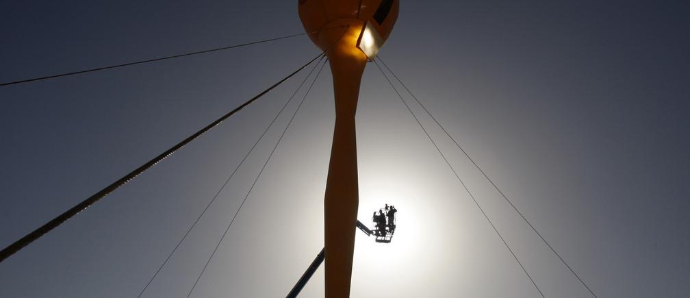 A crane lifts a labourer at a construction site for a hybrid solar power station on Kibbutz Samar February 16, 2009.