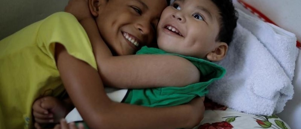 """Daniel Vieira, who is two years old, and was born with microcephaly, is greeted by his brother at their house in Olinda, Brazil, August 7, 2018. During her pregnancy, Daniel's mother Jackeline Vieira de Souza learned that her son had microcephaly. """"When he was born, I fell in love with him because I knew he would be a good thing in my life, even with the difficulties I would have to face."""" Daniel's father separated from Jackeline shortly after learning that his son had microcephaly. He pays a small amount of family support every month, in addition to a monthly check that Jackeline gets from the government. It takes several hours to travel by bus between their home in Olinda and Recife, where Daniel goes for treatments. Lately, those trips are somewhat less frequent, and Jackeline believes Daniel's health is more stable. She has no illusions that her son will ever walk, eat on his own or live a normal life. Yet in many ways she is grateful for her """"miracle"""" baby, who she says makes her feel """"happy and more accomplished."""""""