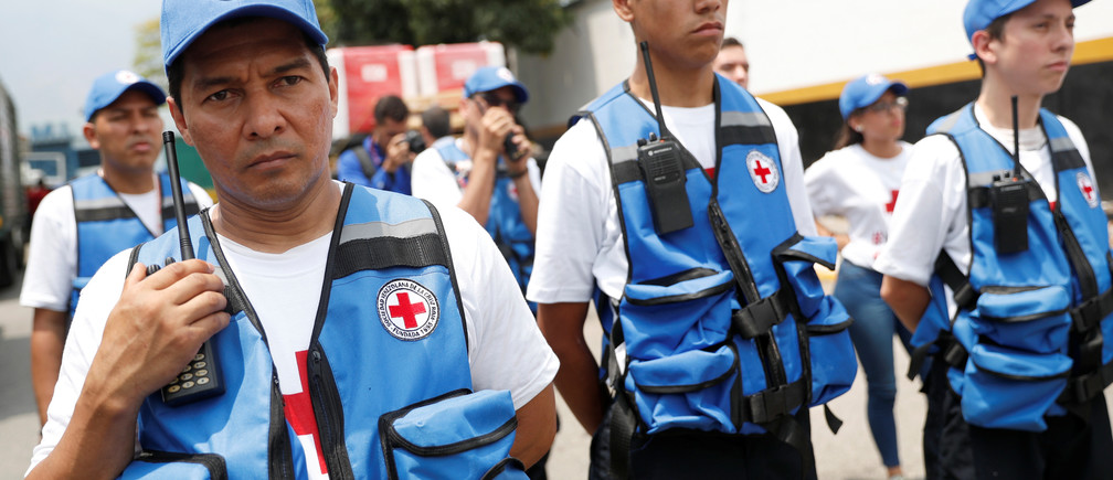 Workers of Venezuelan Red Cross stand next to trucks with logo of the International Federation of Red Cross and Red Crescent Societies (IFRC) carrying humanitarian aid, at a warehouse where the aid will be stored, in Caracas, Venezuela, April 16, 2019. REUTERS/Carlos Garcia Rawlins - RC1BA52F6660