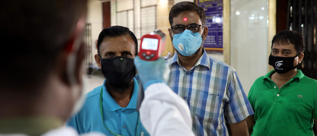 A security personnel checks the body temperature of customers with a thermal scanner at the entrance to a bank amid the coronavirus disease (COVID-19) outbreak in Dhaka, Bangladesh, April 2, 2020. REUTERS/Mohammad Ponir Hossain - RC2CWF99V9I9