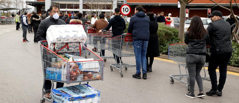 Un client masqué part faire ses courses alors que d'autres clients font la queue pour entrer chez un grossiste Costco à Chingford, en Grande-Bretagne, le 15 mars 2020.