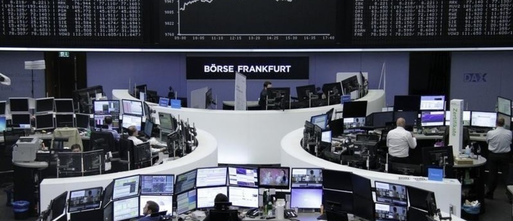 Traders work at their desks in front of the German share price index, DAX board, at the stock exchange in Frankfurt, Germany, April 13, 2016.