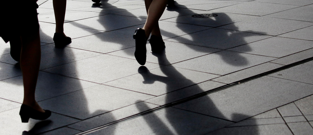Female office workers wearing high heels and clothes of the same colour walk at a business district in Tokyo, Japan, June 4, 2019. REUTERS/Kim Kyung-Hoon - RC13C7A39000
