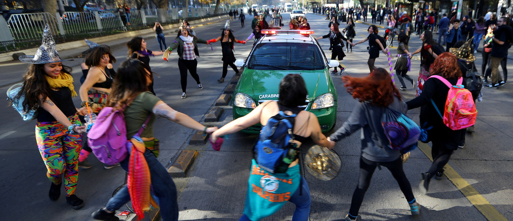 Demonstrators surround a police vehicle during a march against sexism and gender violence in Santiago, Chile.