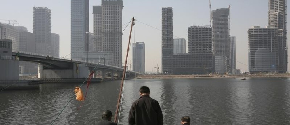 Residents fish with nets on the banks of the Hai River in Tianjin's Binhai New Area, where the government is building its Yujiapu financial center October 23, 2012. The towers in Tianjin's Yujiapu Financial District, and two dozen others on the opposite side of the river, are monuments to the transformation of this once-rundown northern city of 13 million into the country's fastest growing region last year. Picture taken October 23, 2012. REUTERS/Michael Martina (CHINA - Tags: BUSINESS POLITICS CONSTRUCTION) - RTR39ZT3