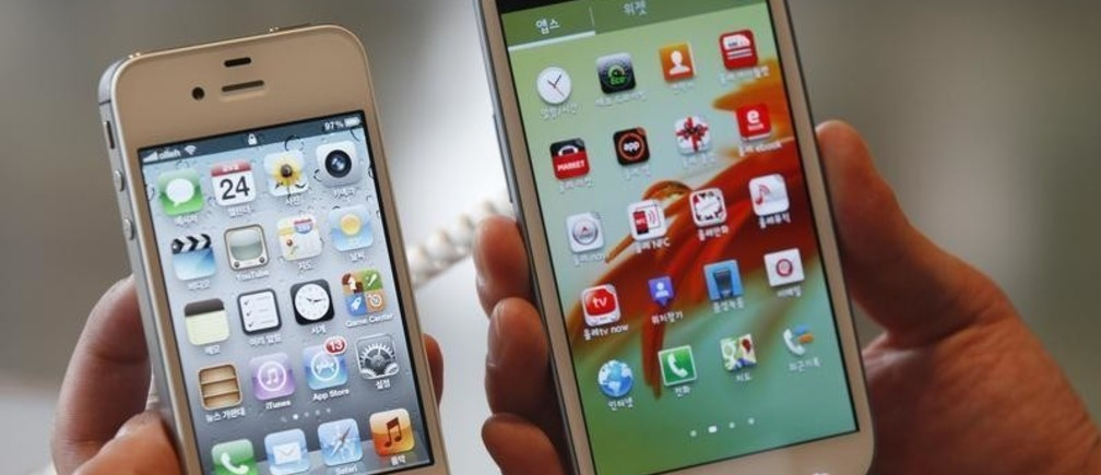 An employee poses as he holds Apple's iPhone 4s (L) and Samsung's Galaxy S III at a store in Seoul August 24, 2012. Samsung Electronics Co's flagship Galaxy smartphone looks very similar to Apple's iPhone, but the South Korean firm has not violated the iPhone design, a Seoul court ruled on Friday. The South Korean ruling comes as the two technology titans are locked in a high-stakes global patent battle that mirrors a fierce rivalry for industry supremacy between two companies that control more than half the world's smartphone sales.