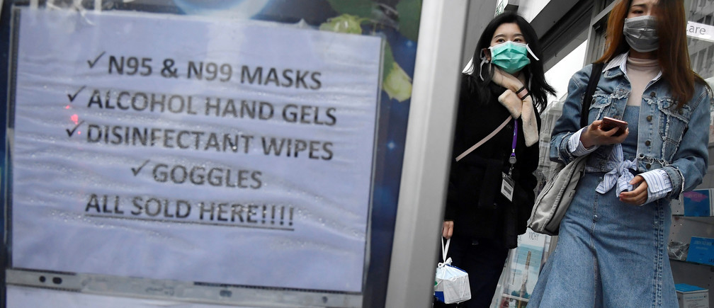 Customers wearing protective face masks are seen leaving a pharmacy in London, Britain, March 4, 2020.