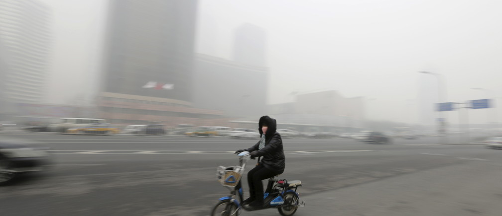 A woman wearing a mask cycles amid heavy smog in Beijing's Guomao area, China, November 30, 2015. REUTERS/Jason Lee