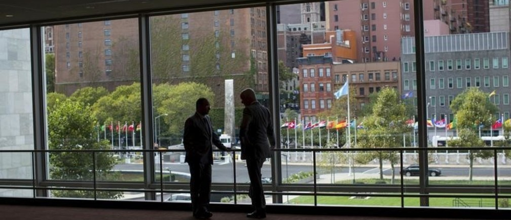 """Two diplomats talk in front of a window between the Secretariat and Assembly Buildings at the United Nations headquarters in New York City, September 21, 2015. As leaders from almost 200 nations gather for the annual general assembly at the United Nations, the world body created 70 years ago, Reuters photographer Mike Segar documented quieter moments at the famed 18-acre headquarters on Manhattan's East Side. The U.N., established as the successor to the failed League of Nations after World War Two to prevent a similar conflict from occurring again, attracts more than a million visitors every year to its iconic New York site. The marathon of speeches and meetings this year will address issues from the migrant crisis in Europe to climate change and the fight against terrorism. REUTERS/Mike SegarPICTURE 10 OF 30 FOR WIDER IMAGE STORY """"INSIDE THE UNITED NATIONS HEADQUARTERS""""SEARCH """"INSIDE UN"""" FOR ALL IMAGES  - GF10000219208"""