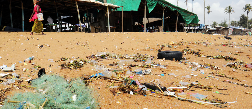 A woman walks past plastic items and other debris on Vridi beach in Abidjan, Ivory Coast November 21, 2018. REUTERS/Thierry Gouegnon - RC1B90C6CAB0