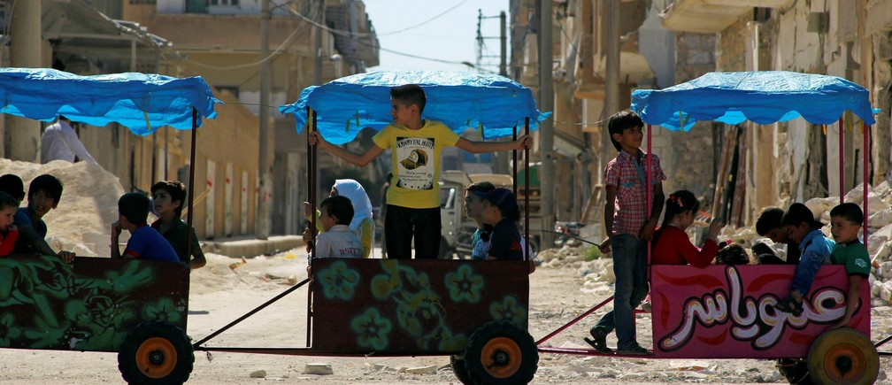 Children ride in carts on the third day of Eid al-Adha in the rebel controlled city of Idlib, Syria September 14, 2016.
