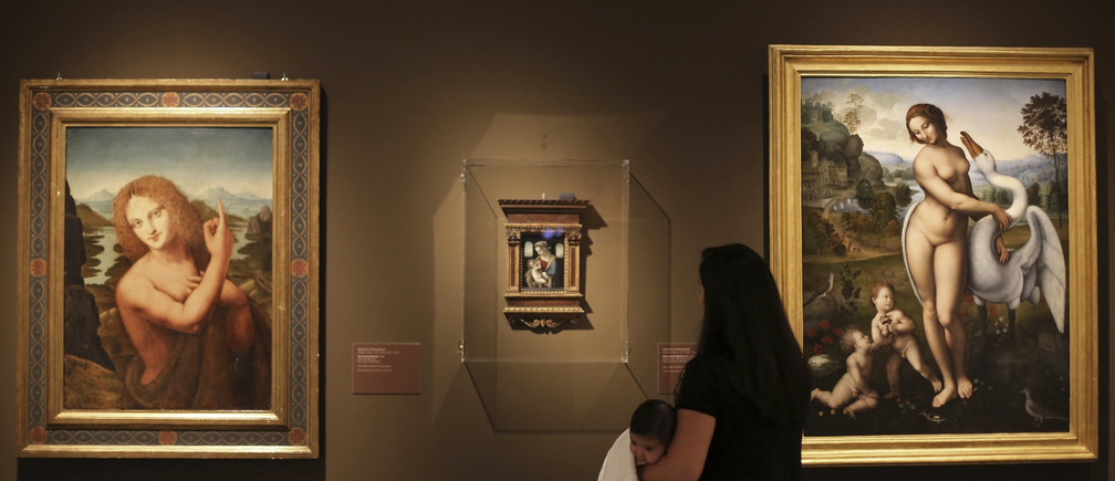 """A visitor carrying her baby looks at the """"San John the Baptist"""" (L) and the """"Madonna with Child"""", paintings by artist Marco D'Oggiono, and """"Leda and the Swan"""" (R), a painting by artist Leonardo Da Vinci, during the """"Masters of the Renaissance, Masterpieces from Italy"""" exhibition at the Bank of Brazil Cultural Centre in Sao Paulo July 13, 2013. The exhibition will run from July 13 to September 23.  REUTERS/Nacho Doce (BRAZIL - Tags: SOCIETY) - GM1E97E0IME01"""