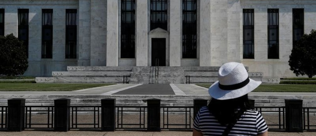 A woman takes a photograph of the Federal Reserve building in Washington, U.S., July 16, 2018.