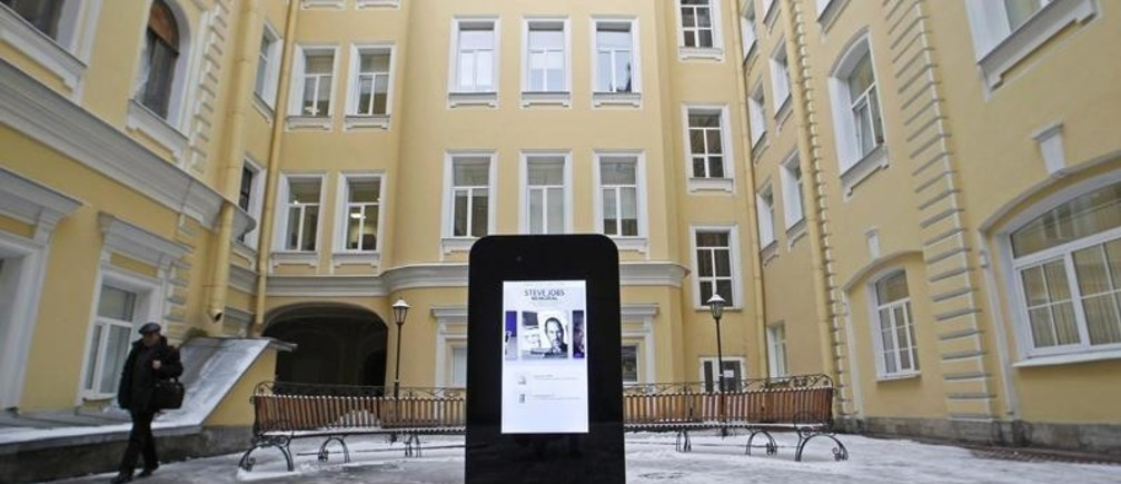 A man walks past a recently erected iPhone-shaped monument in memory of Apple's late co-founder Steve Jobs in the yard of the State University of Information Technologies, Mechanics and Optics in St. Petersburg January 10, 2013. The 188cm (74 inch) -tall interactive glass and metal sculpture, designed by Gleb Tarasov, is a wifi hotspot and can withstand temperatures down to minus 30 degrees Celsius (minus 22 degrees Fahrenheit), according to local media. REUTERS/Alexander Demianchuk (RUSSIA - Tags: SOCIETY SCIENCE TECHNOLOGY BUSINESS) - GM1E91A1HYM01