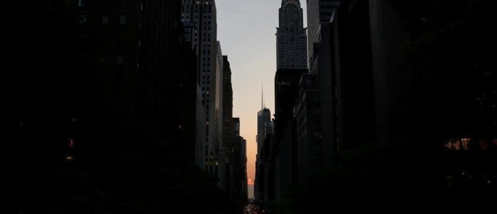 A cloud blocks the sunset on 42nd St in Manhattan during the phenomenon known as Manhattanhenge in New York City, New York, U.S. May 29, 2018. REUTERS/Joe Penney - RC18DCF01D40