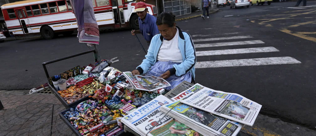 A woman sells newspapers and cigarettes at a cart in downtown San Salvador January 31, 2014.