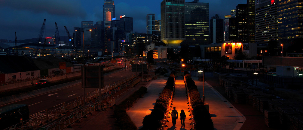 People walk on a pavement at Hong Kong's financial Central district during sunset May 11, 2011.
