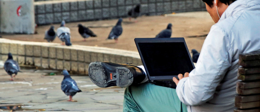 A man uses a laptop computer as pigeons are seen at a park in Tokyo, Japan October 18, 2017.  REUTERS/Toru Hanai - RC1DBD5108F0