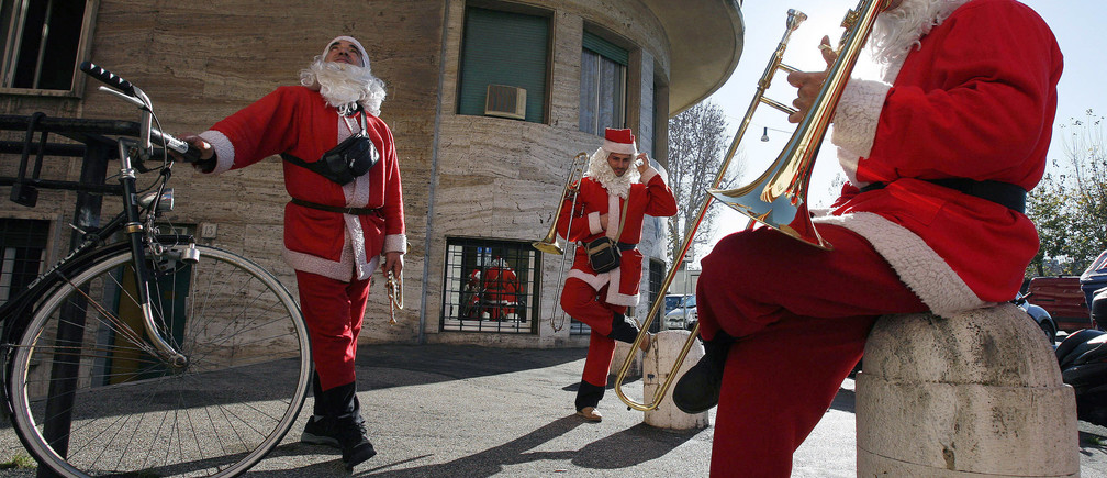Members of a Christmas band (L-R) Carmelo, Giuseppe and Michele take a break in Rome December 12, 2006. For six years, five musicians from the southern Italian town of Fracagnano have been coming to Rome to play Christmas songs in the streets, asking for donations from people who peer out of the window as they hear their music. Only one, Michele, has a fulltime job.   REUTERS/Dario Pignatelli   (ITALY) - GM1DUDLOWIAA
