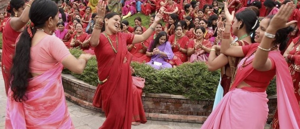 """Women celebrate """"Teej"""" festival at a temple in Kathmandu, September 14, 2007. They pray for a happily married life during the festival."""