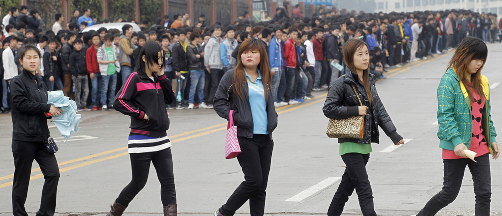 Job seekers cross a road as they queue outside Foxconn recruitment center in Shenzhen, Guangdong province February 22, 2012