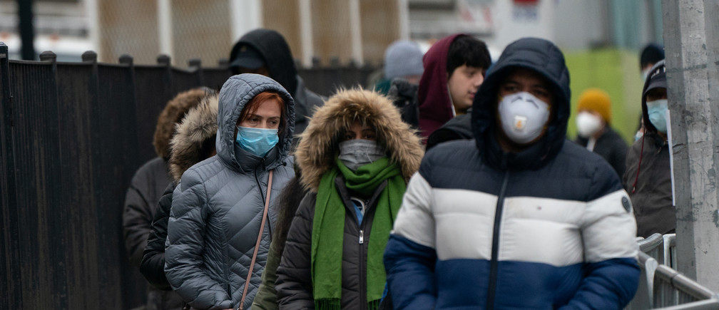 People wait in line to be tested for coronavirus disease (COVID-19) while wearing protective gear, outside Elmhurst Hospital Center in the Queens borough of New York City, U.S., March 30, 2020. REUTERS/Jeenah Moon - RC2FUF9SIGT8