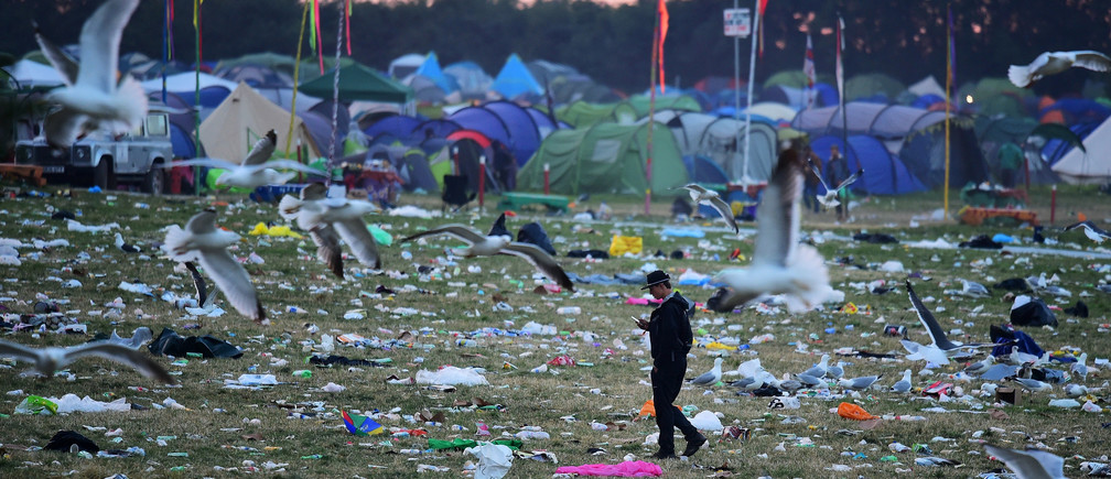 Revellers and detritus are seen near the Pyramid Stage at Worthy Farm in Somerset during the Glastonbury Festival in Britain, June 26, 2017. REUTERS/Dylan Martinez - RC16F704FFF0