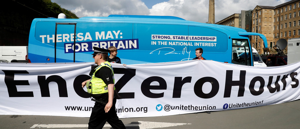 A police officer walks in front of a banner protesting against zero hours contracts in Halifax, United Kingdom.
