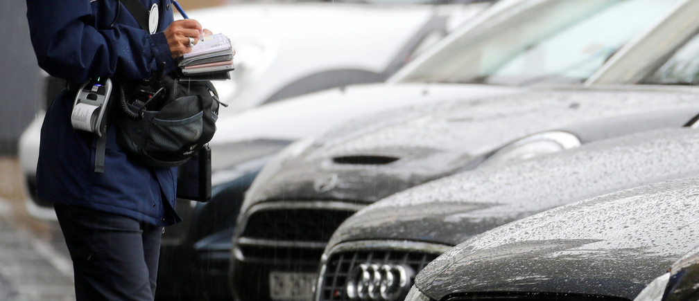 A parking attendant writes a ticket in front of parked cars in Zurich, Switzerland May 20, 2019.