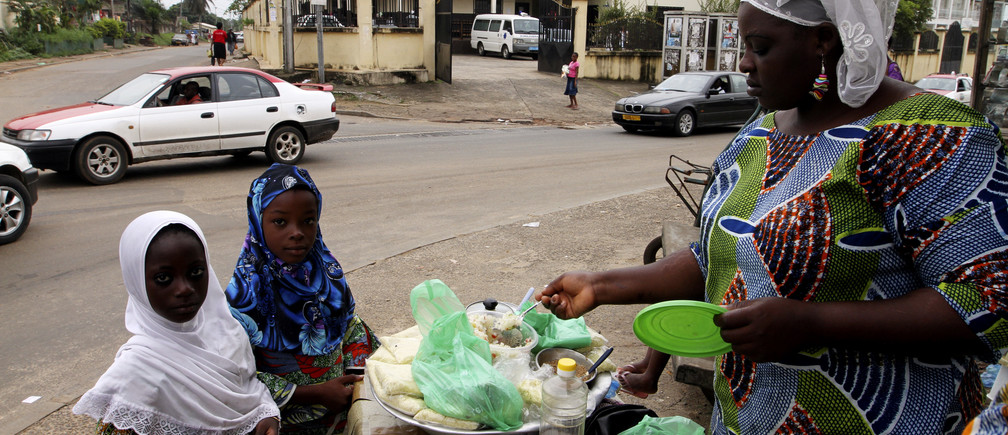 Muslim girls buy food from a street vendor at Okala, an area of Libreville February 14, 2012.