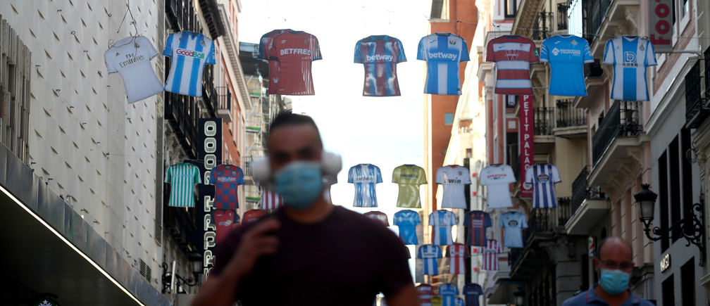 A man walks under decorations depicting shirts of Spanish First Division soccer clubs days before resuming the competition amid the coronavirus disease (COVID-19) outbreak, in Madrid, Spain, June 8, 2020. REUTERS/Sergio Perez - RC275H904D9X