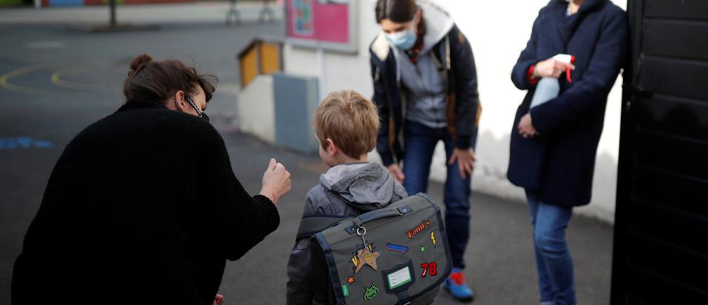 Los maestros que usan máscaras faciales de protección dan la bienvenida a los escolares que entran en su escuela durante su reapertura en Saint-Sebastien-sur-Loire, cerca de Nantes, ya que una pequeña parte de los niños franceses regresan a sus escuelas con nuevas reglas y distanciamiento social durante el brote de la enfermedad coronavirus (COVID-19) en Francia, el 12 de mayo de 2020.