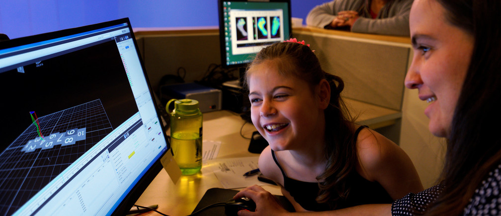 Ryleah Geisner, 8, laughs as she looks at a computer image of herself walking with reflective and surface EMG sensors attached to her body in the Center for Gait and Movement Analysis lab at Children's Hospital Colorado in Aurora, Colorado, U.S., February 9, 2017 with lab engineer Kayla Burnim (R.)  Ryleah has cerebral palsy, a congenital disorder of movement, muscle tone, or posture. The lab was using 3-D motion capture technology to analyze Ryleah's body movement and muscle activity while walking and that data will then be used to formulate a treatment plan for her. In the background is Ryleah's grandmother Sandy Geisner. Picture taken on February 9, 2017.  REUTERS/Rick Wilking - RC1C3DE6D970
