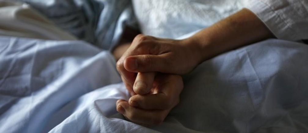 A woman holds the hand of her mother who is dying from cancer during her final hours at a palliative care hospital in Winnipeg July 24, 2010. Picture taken July 24, 2010.      REUTERS/Shaun Best   (CANADA - Tags: HEALTH) - GM1E69F1TP401