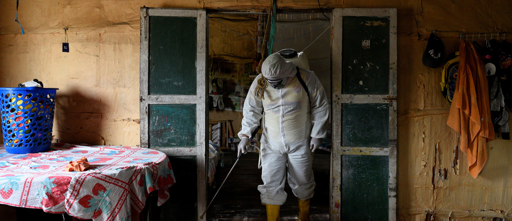 "A local volunteer, who is helping to disinfect buildings in his town during the coronavirus disease (COVID-19) outbreak, wears protective clothing as he disinfects a home with a chlorine solution, in Zapotal, Ecuador, May 2, 2020. REUTERS/Santiago Arcos     SEARCH ""RURAL ECUADOR COVID-19"" FOR THIS STORY. SEARCH ""WIDER IMAGE"" FOR ALL STORIES. - RC2CSG92KHWL"